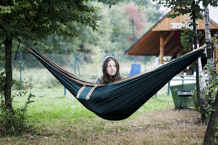 a woman sitting in a hammock between two trees