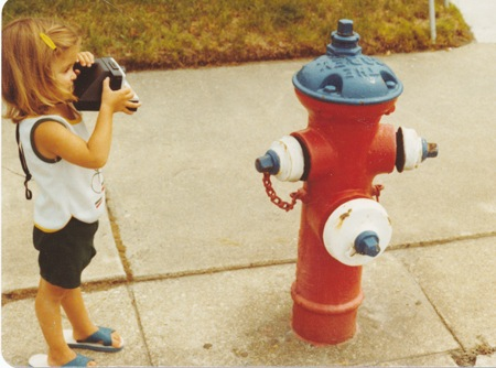 picture of a little girl with a polaroid camera and a fire hydrant practicing photography