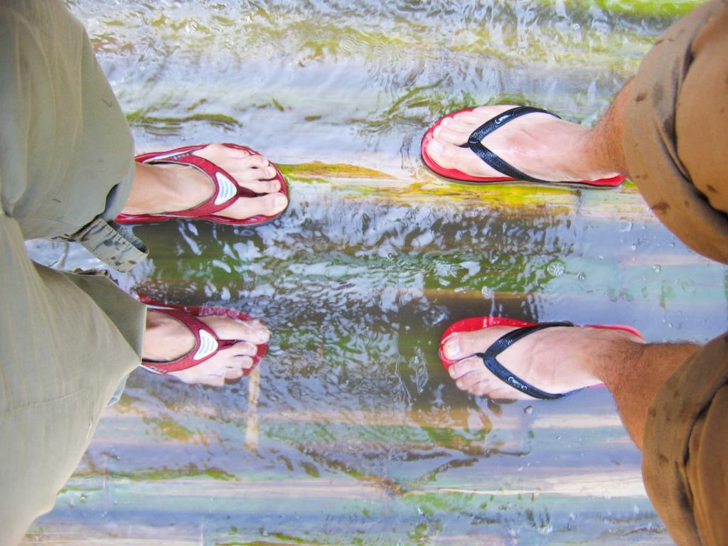 feet with flip flops standing on a bamboo raft in the river