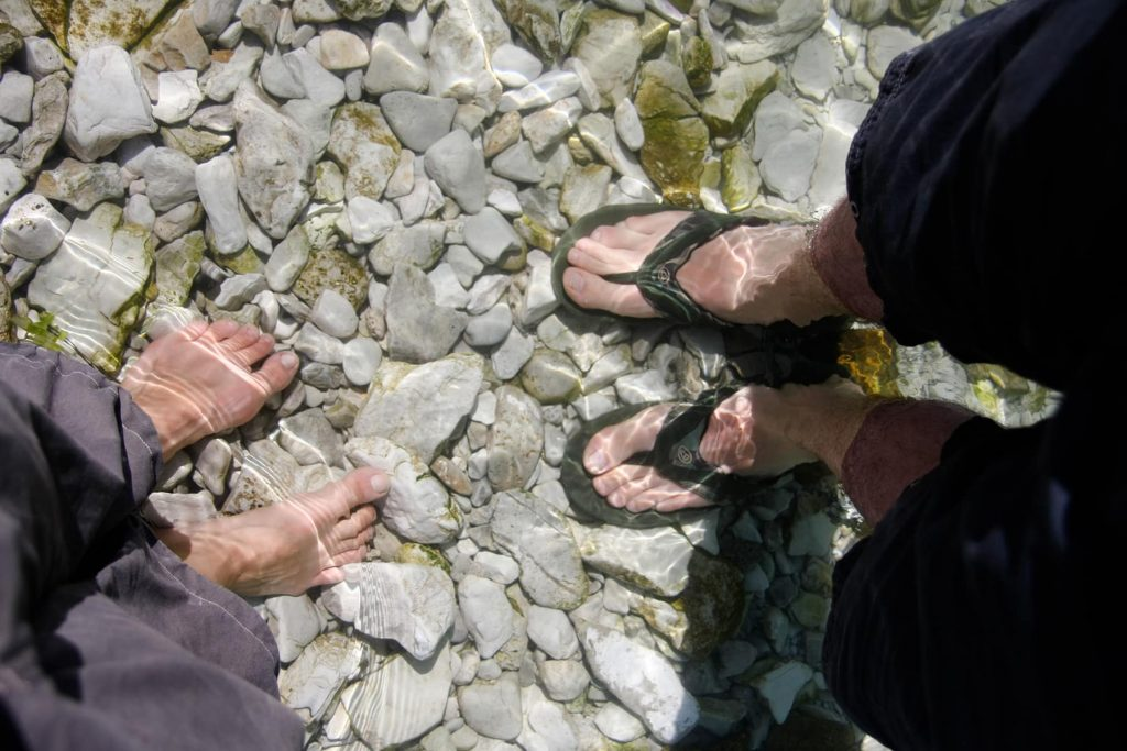 feet under water with reflections on stones