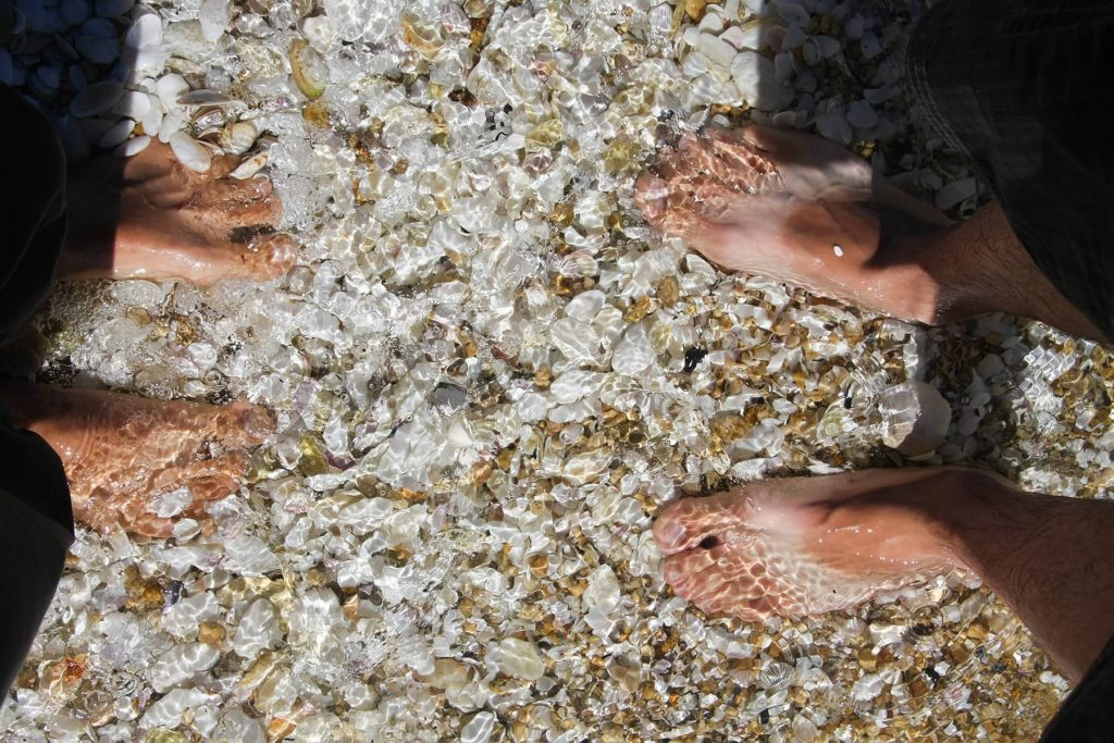 feet on rocks under water