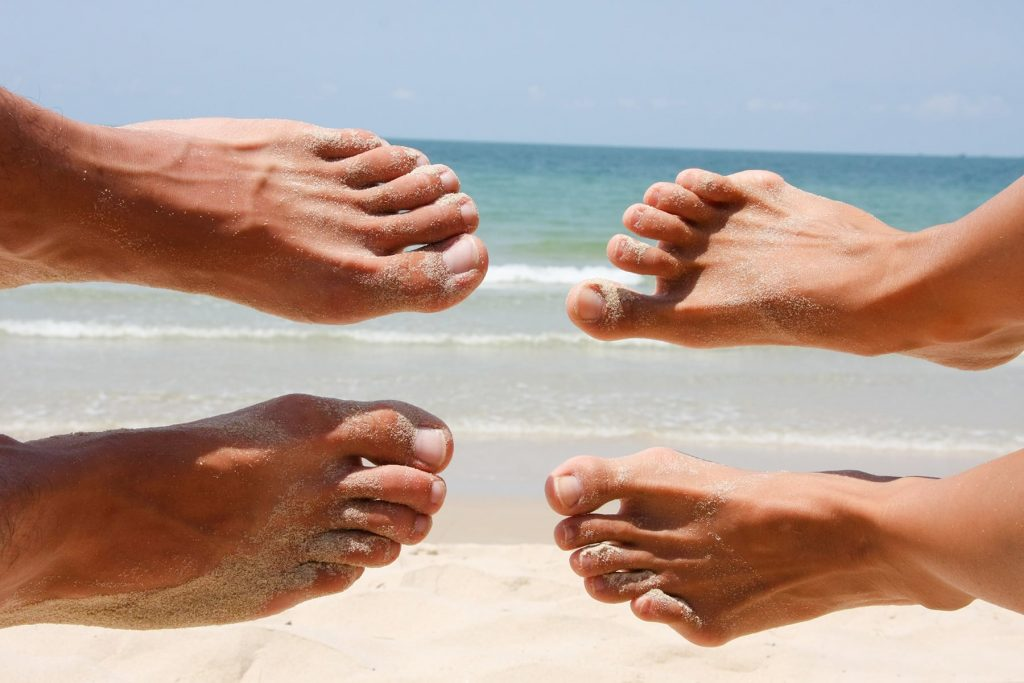 feet hanging in front of the ocean on a sandy beach