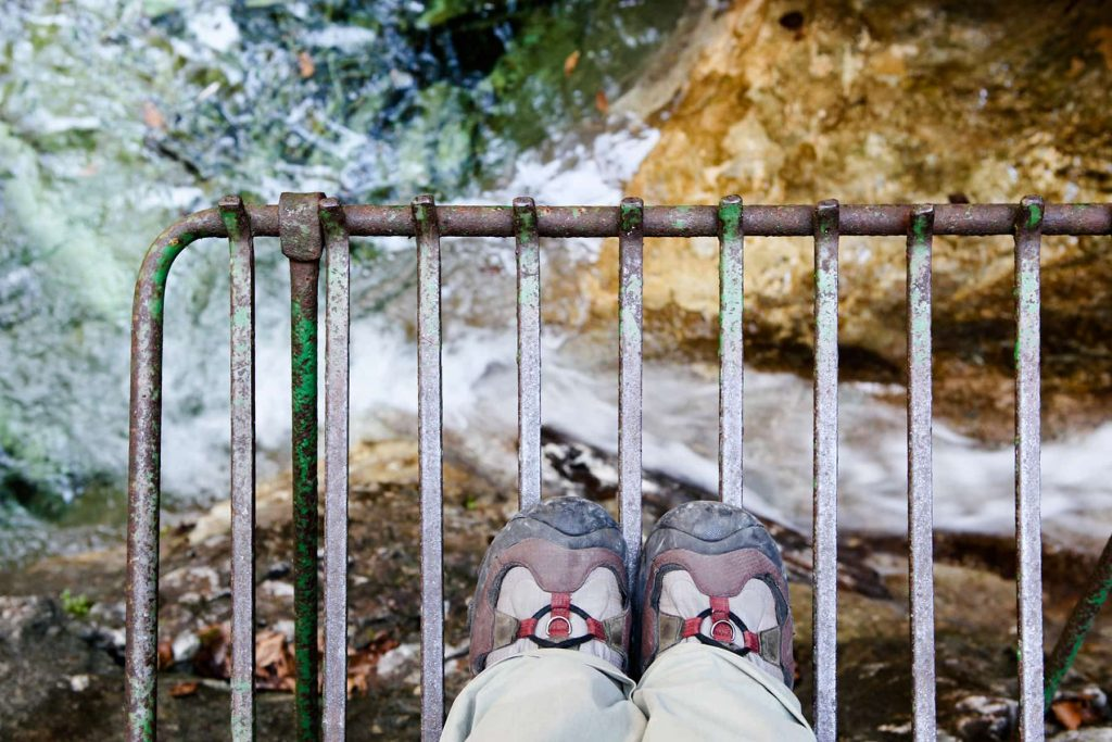 standing on a grate while hiking over a large waterfall