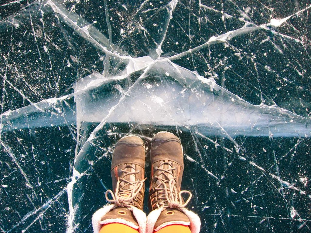 carefully balancing on the ice of a frozen lake