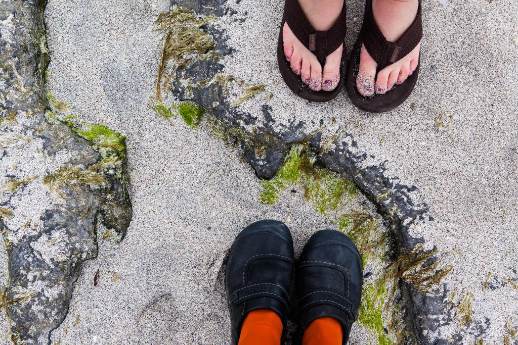 standing on the beach with sand moss and rocks with a friend