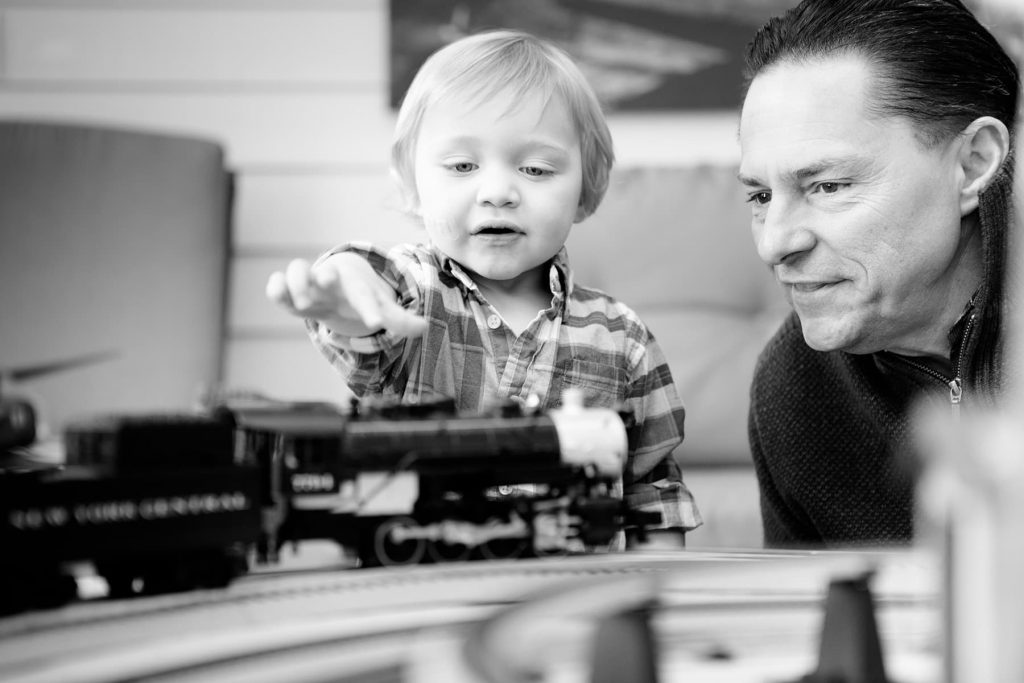 a father plays with the model train set with his son