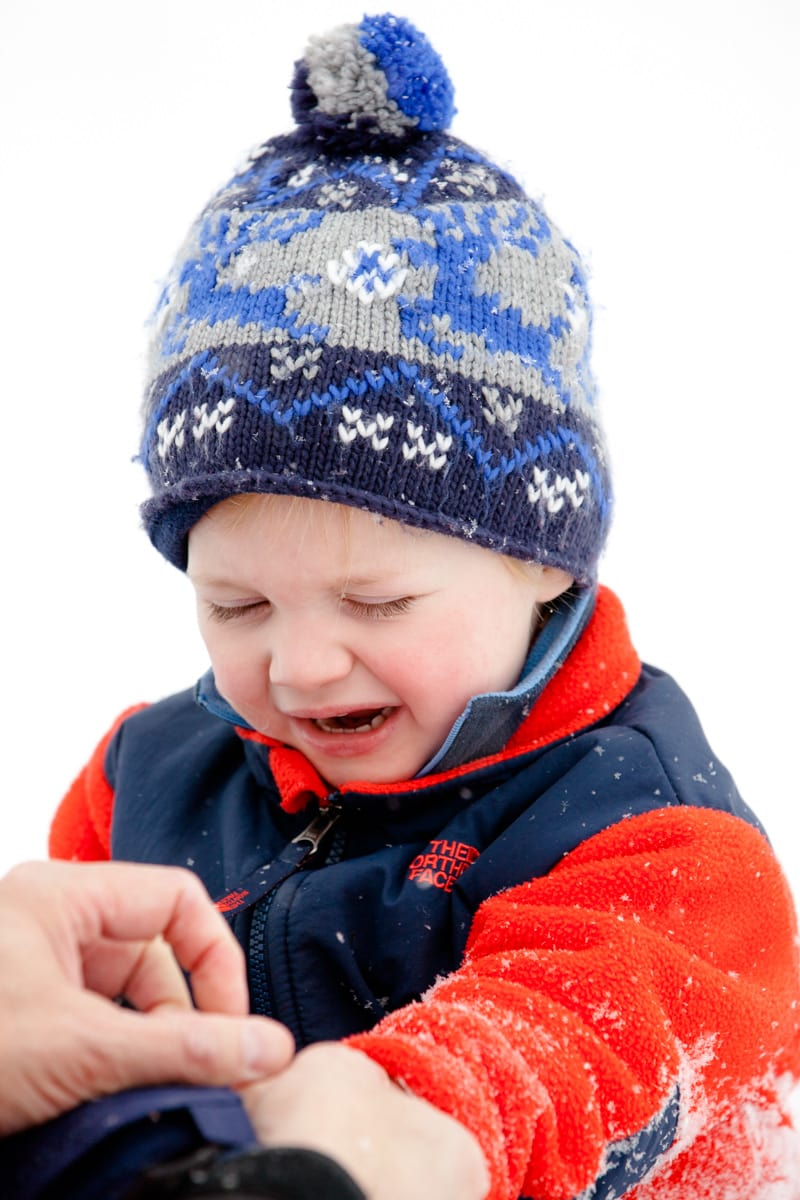 a boy is crying because his hands are cold in the snow