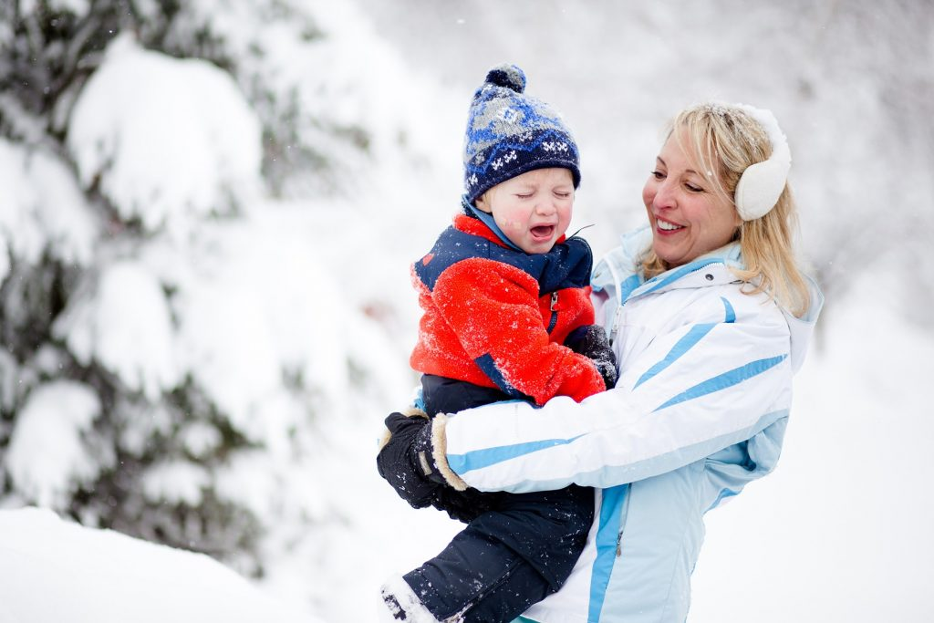 mama holds her son in the snow and he is crying