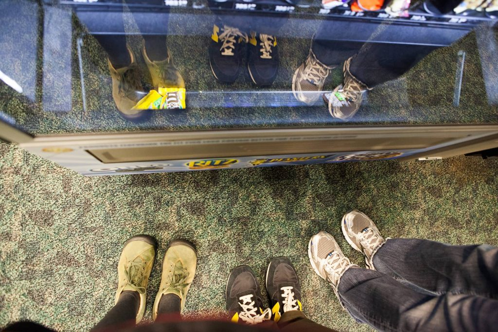 reflection of feet in the window of a vending machine