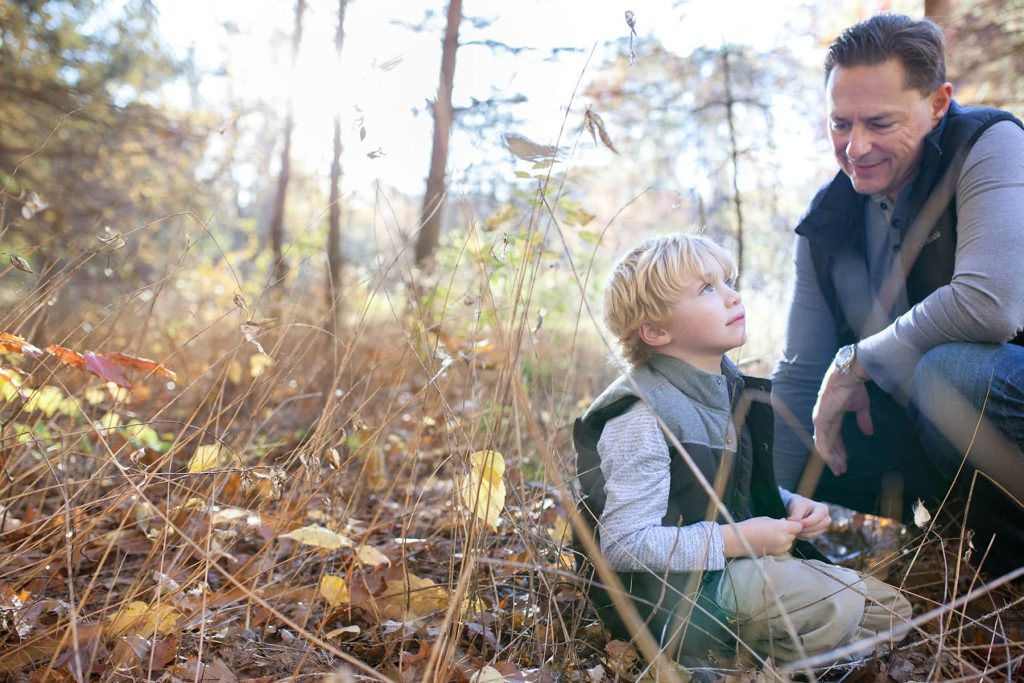a boy and his father sit in the woods thinking