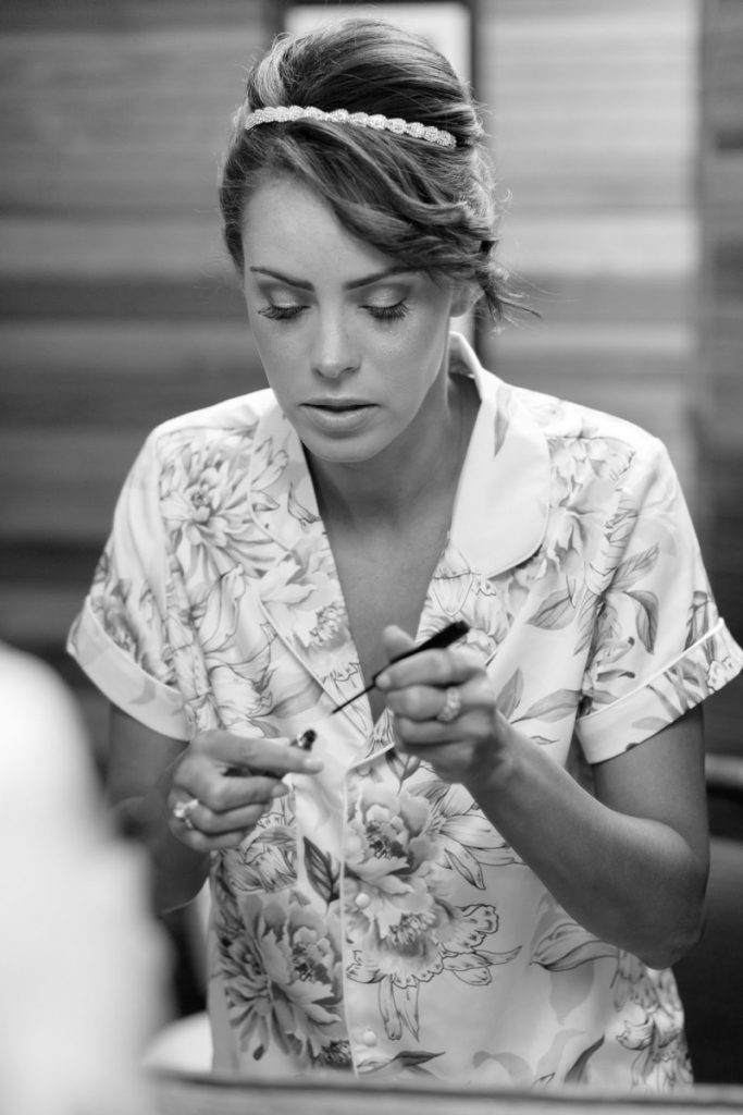 bride puts on her makeup during her getting ready pictures