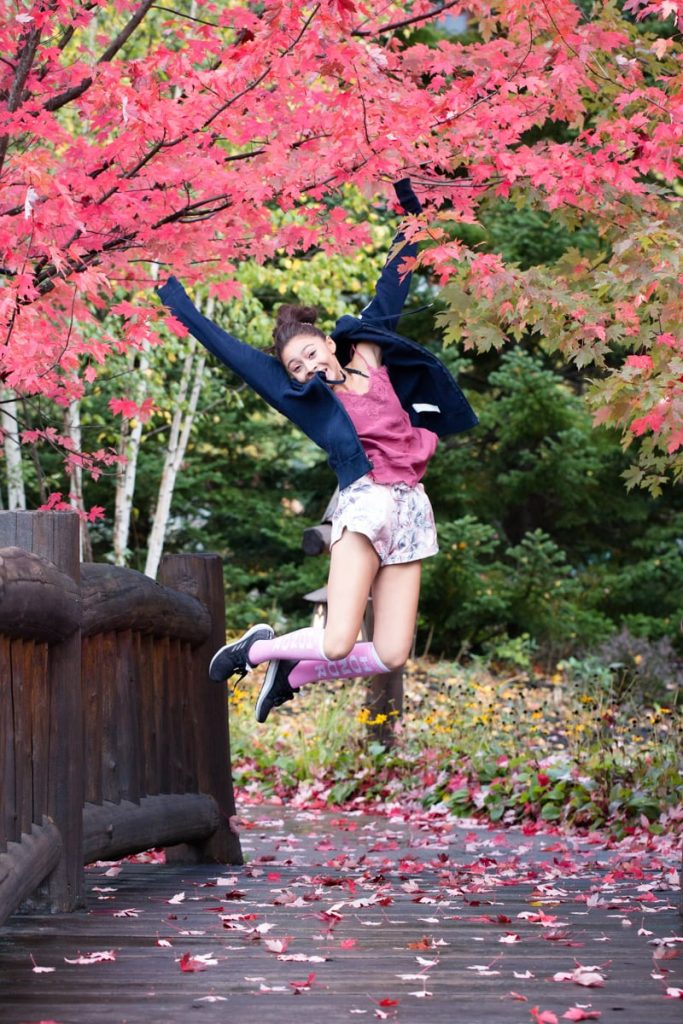little girl jumps in the colored trees