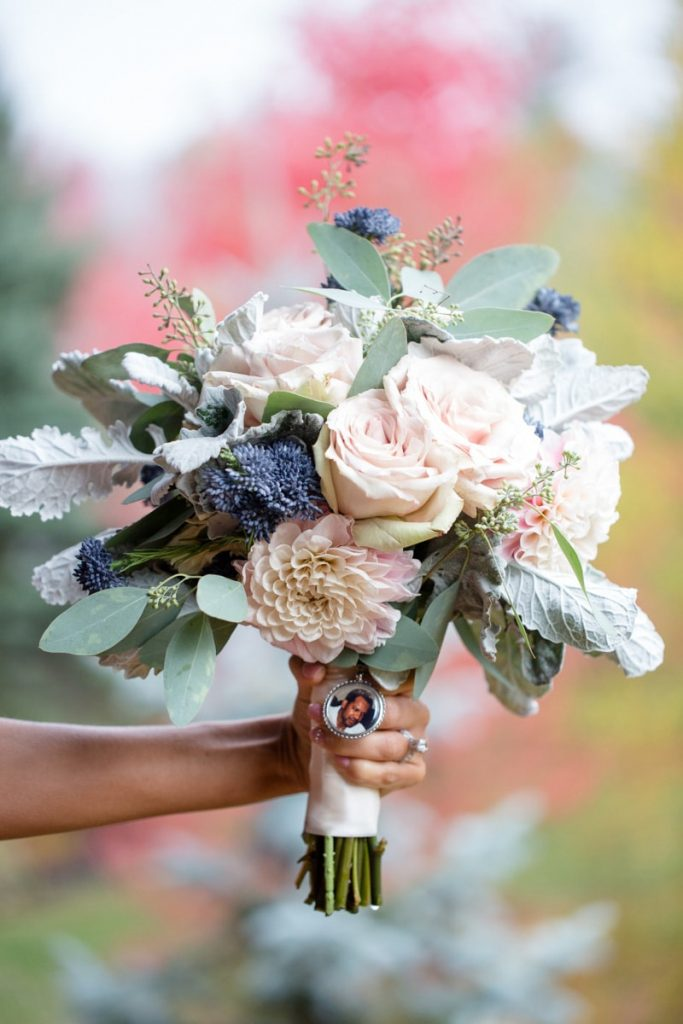 bride holds her beautiful bouquet in front of a bright red maple tree