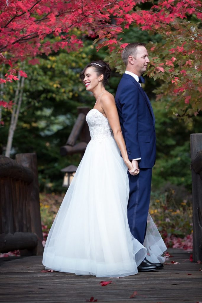 husband and wife prepare for their first look by standing back to back