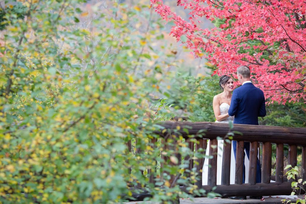 bride and groom stand in the fall foliage on a bridge during their portrait session