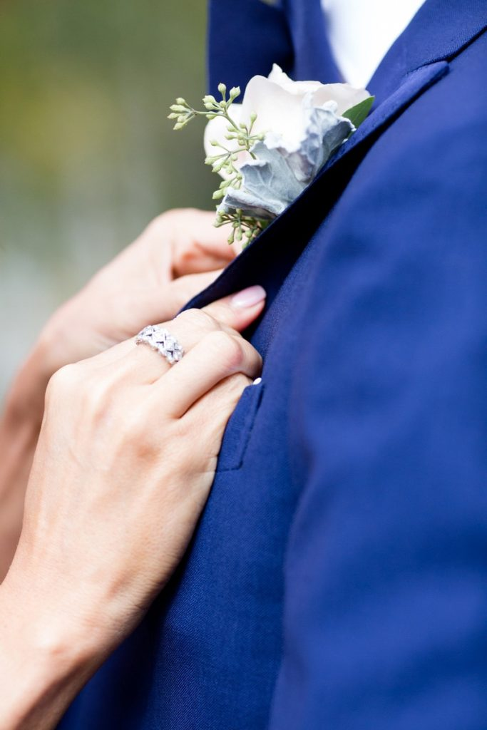 bride puts her groom's boutonniere on