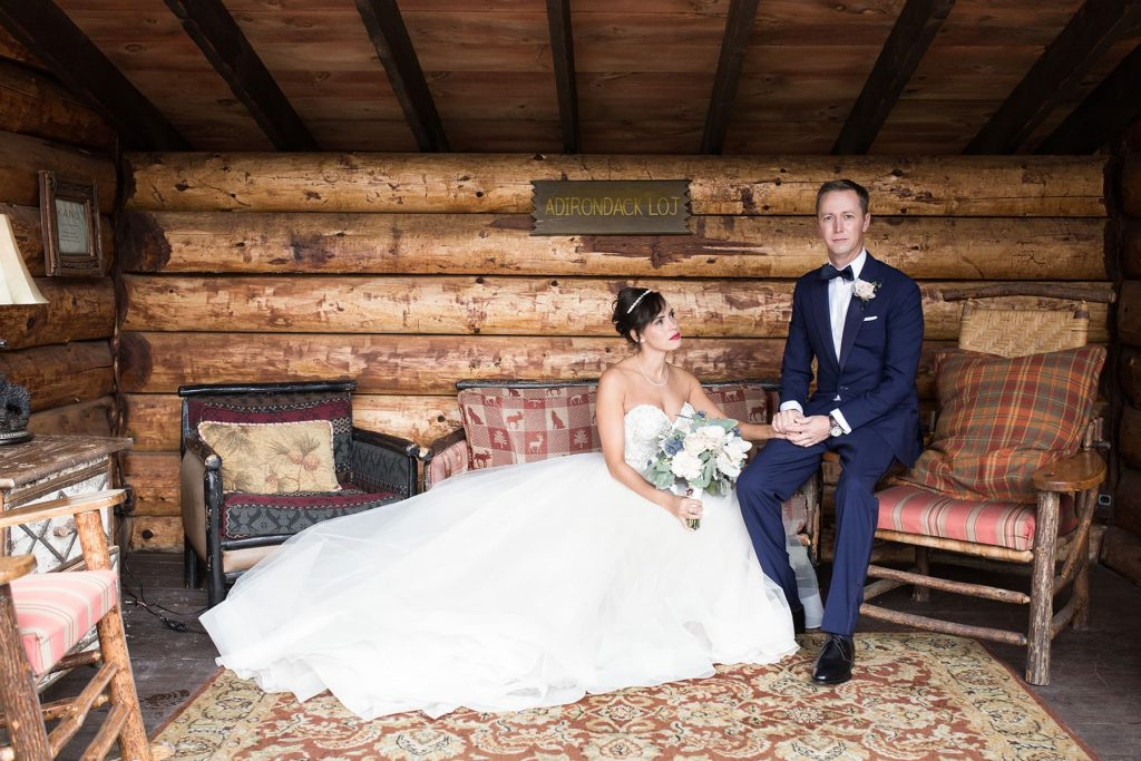 groom and bride sit in a log cabin
