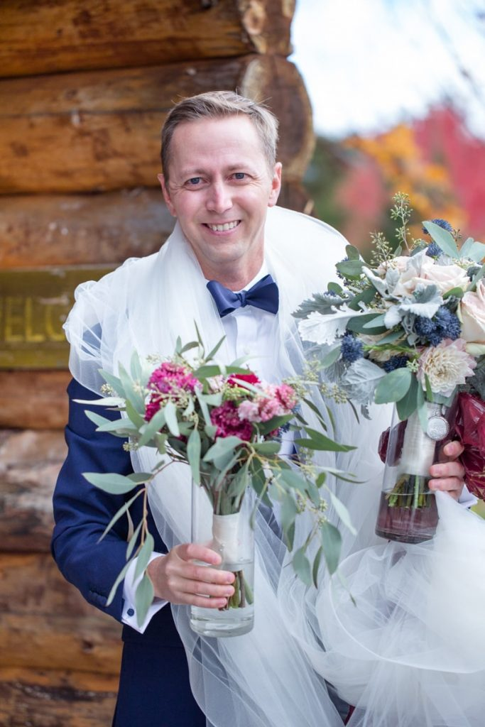 groom carries bouquets