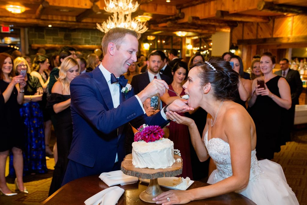 groom feeds bride cake during the cake cutting