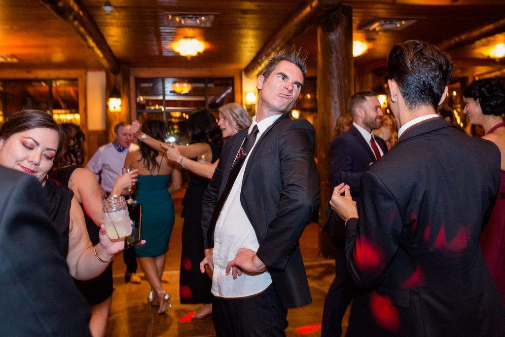 man makes a funny face while dancing at a destination wedding