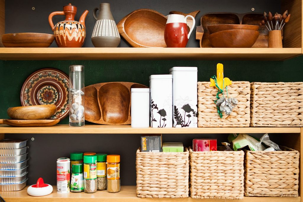 a wonderfully organized kitchen with straw baskets and containers