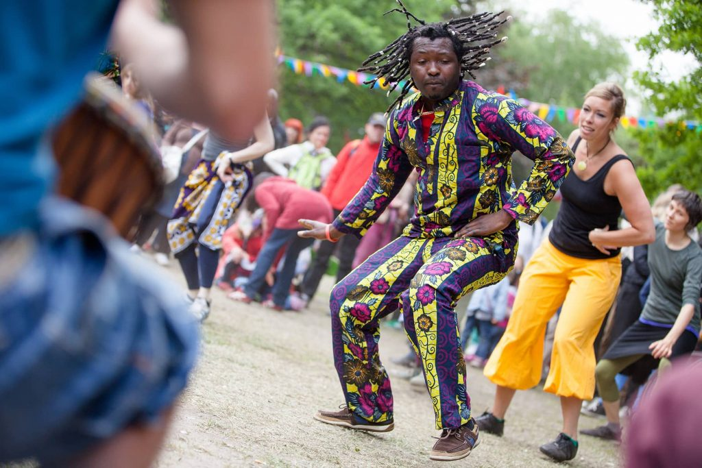 a man dances to drums in the park during a music festival