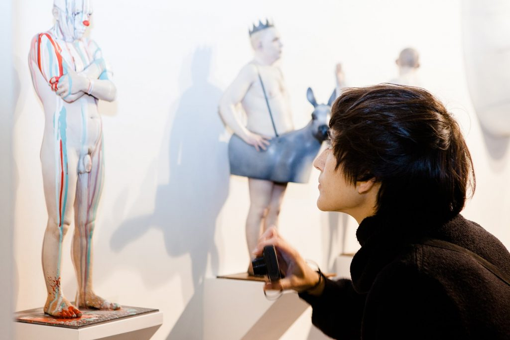 a person photographs and inspects a small, naked human statue of a man
