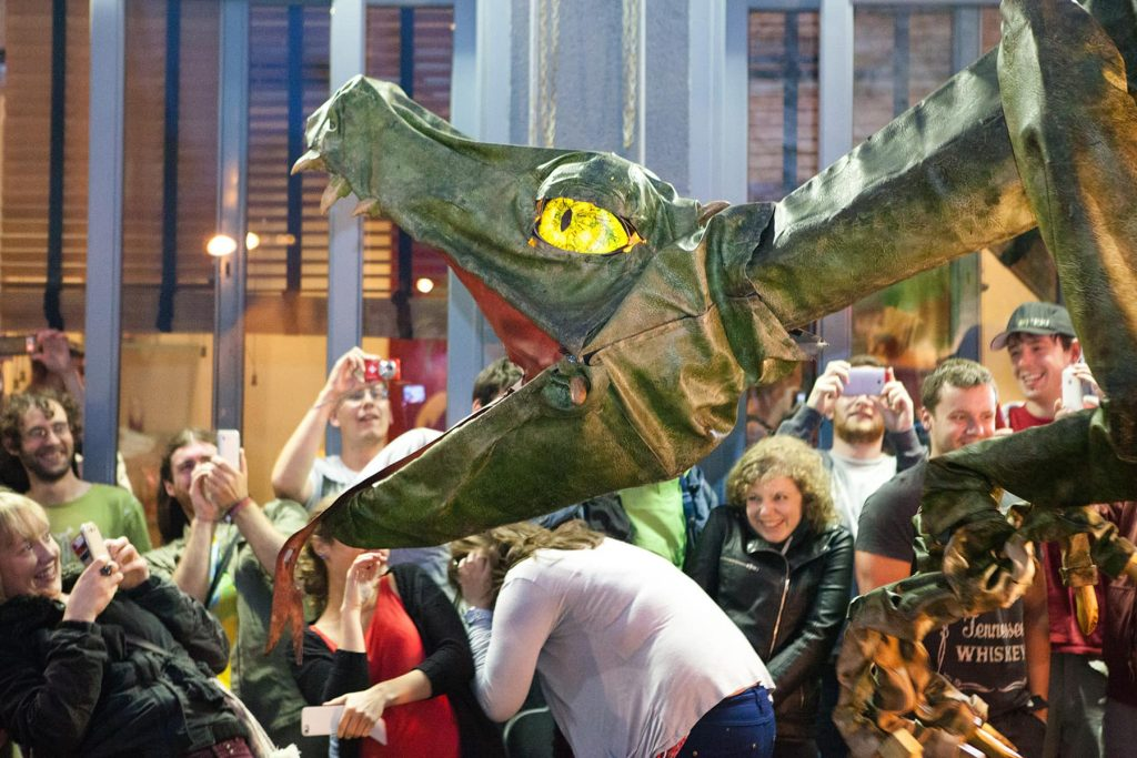 a dragon attacks the crowd during a fun parade