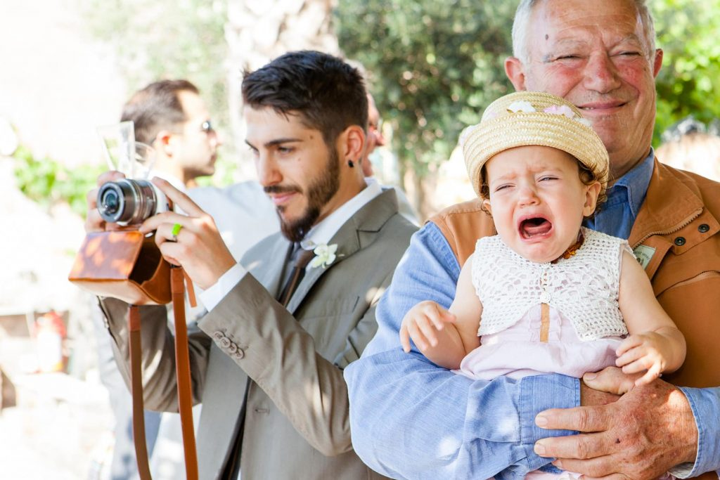 grandpa holds crying baby while man photographs guests during cocktail hour