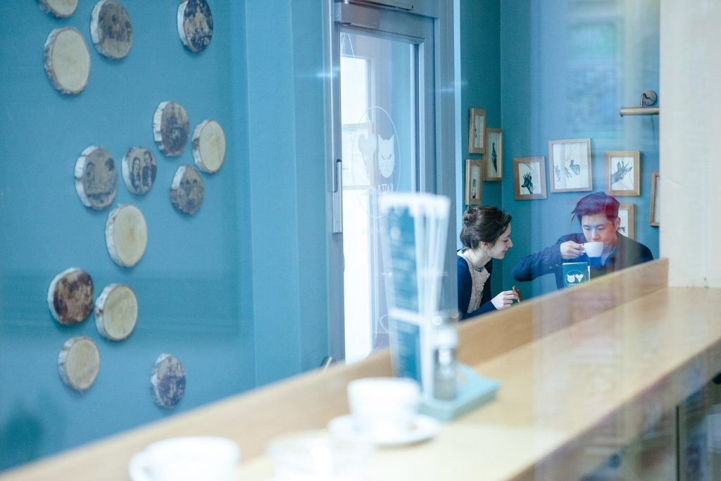 cafe with pictures on the wall and a countertop through a reflection