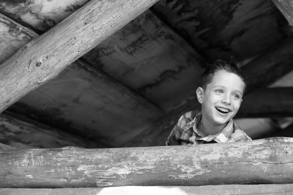 young boy is laughing while looking out of the top of a hut