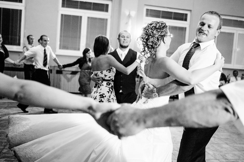best man spins bride around dancing while groom looks from the background