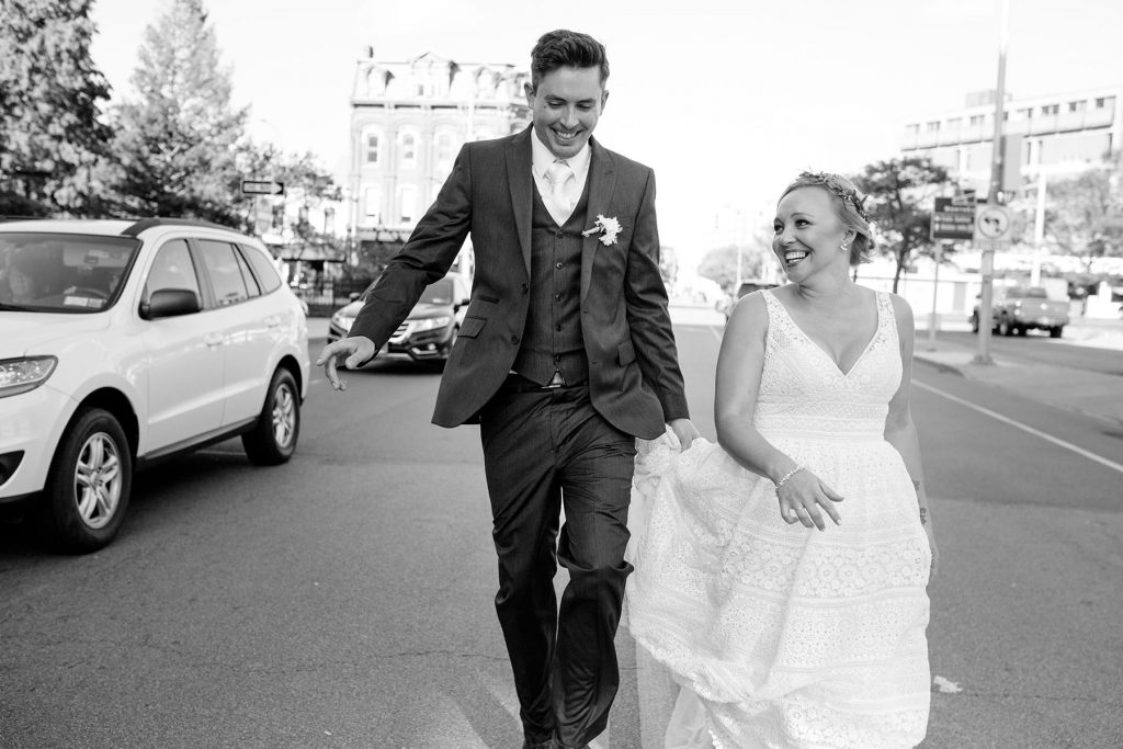 newlyweds run down the middle of a Rochester NY street just after their city wedding