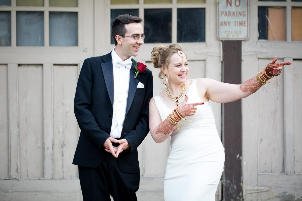 bride points to her parents during the portrait session