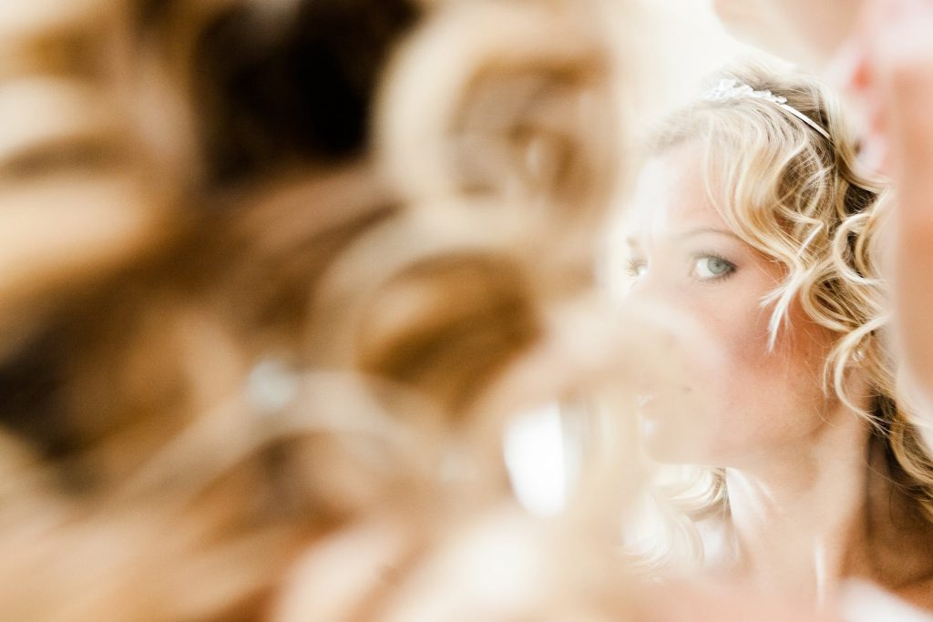 bride checks her earrings while getting ready for her wedding