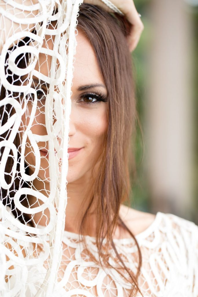 bride covers half of her face with her wedding dress and gives a small smile