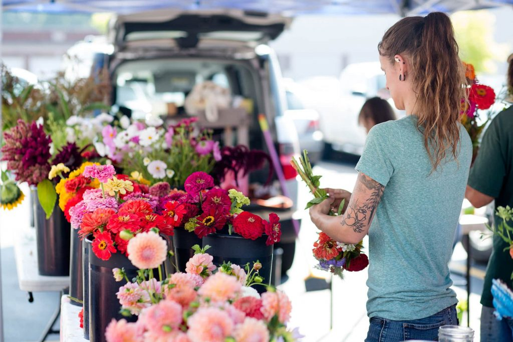 A woman from Chicory Blue Gardens in Spencerport arranges flowers to sell at Brighton Market