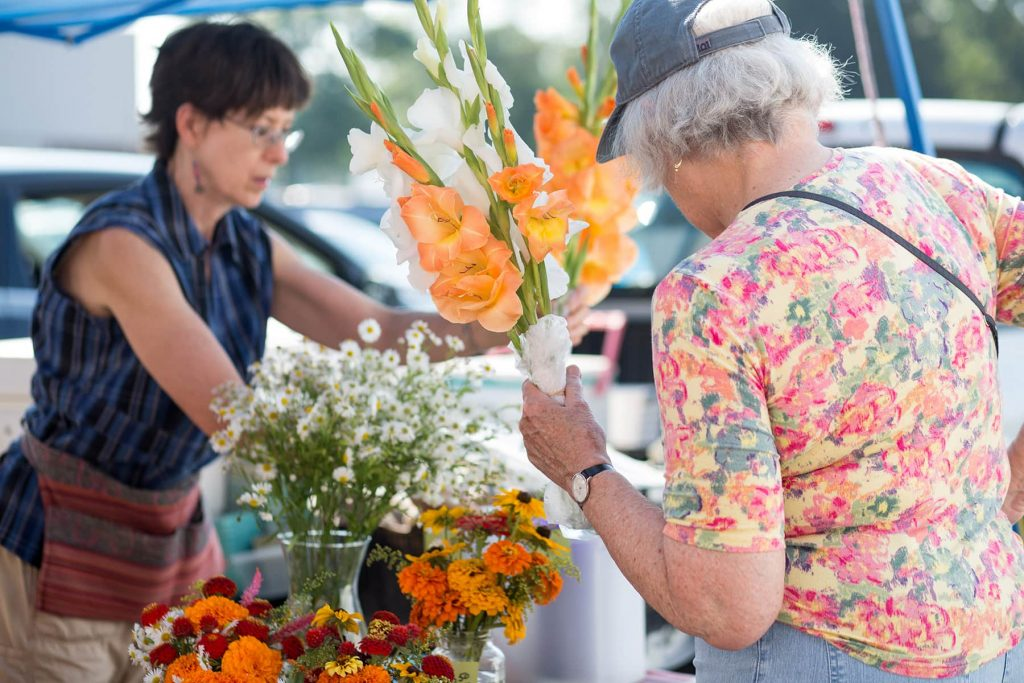 a woman purchases a bouquet of orange flowers