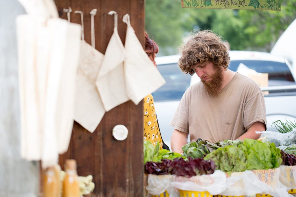 A man from Fellenz Family Farm in Phelps, NY prepares his stand for the market