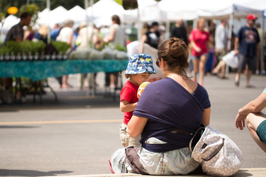 a mother talks to her toddler while babywearing her baby