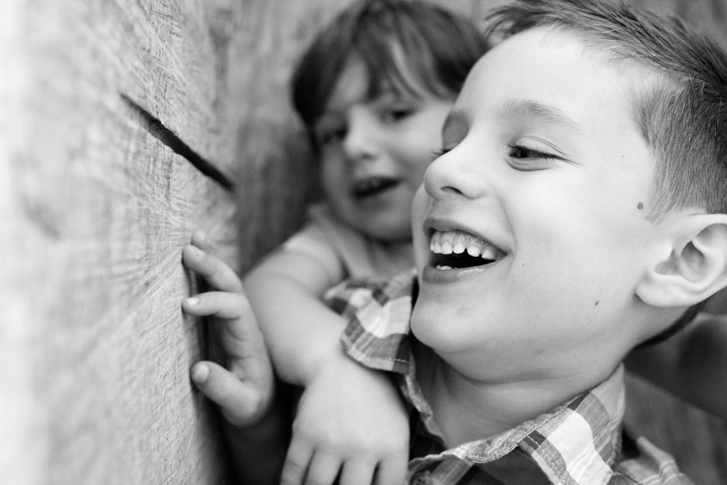 black and white of brothers playing in a hidden fort and laughing
