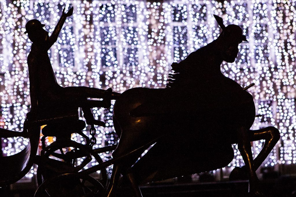 a sleigh rider and a horse with lights on a fountain
