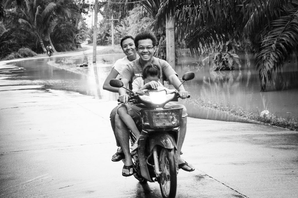 a family rides on a motor bike in the rain and laughs