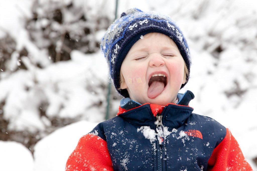 toddler boy catches snow on his tongue in the winter