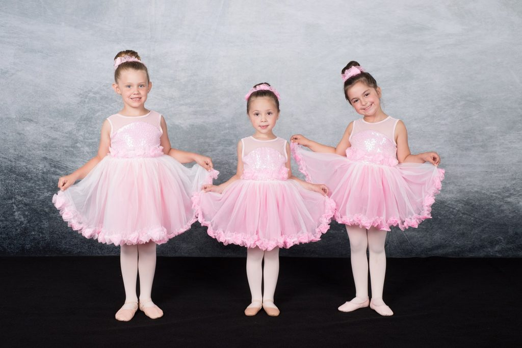 three little ballerinas in pink tutus pose for their picture