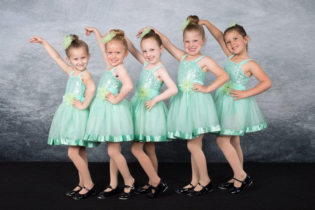 a group of young girls in turquoise dresses pose for their dance class picture