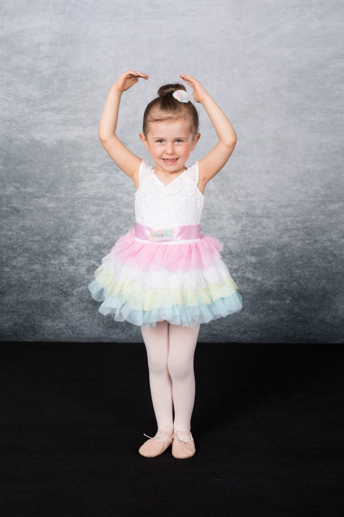 a little girl smiles in her rainbow tutu