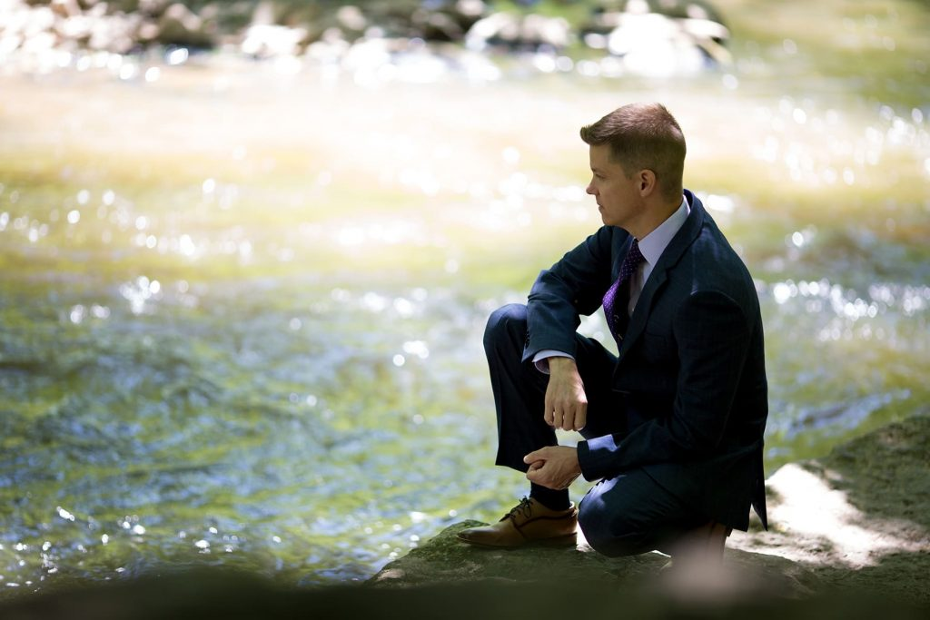 groom is sitting by the water pensive before his wedding