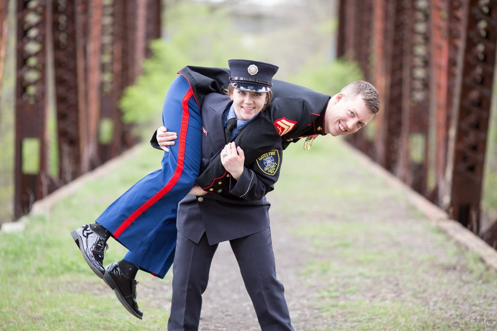 a Rochester Firefighter lifts her husband-to-be over her shoulders in their engagement photo
