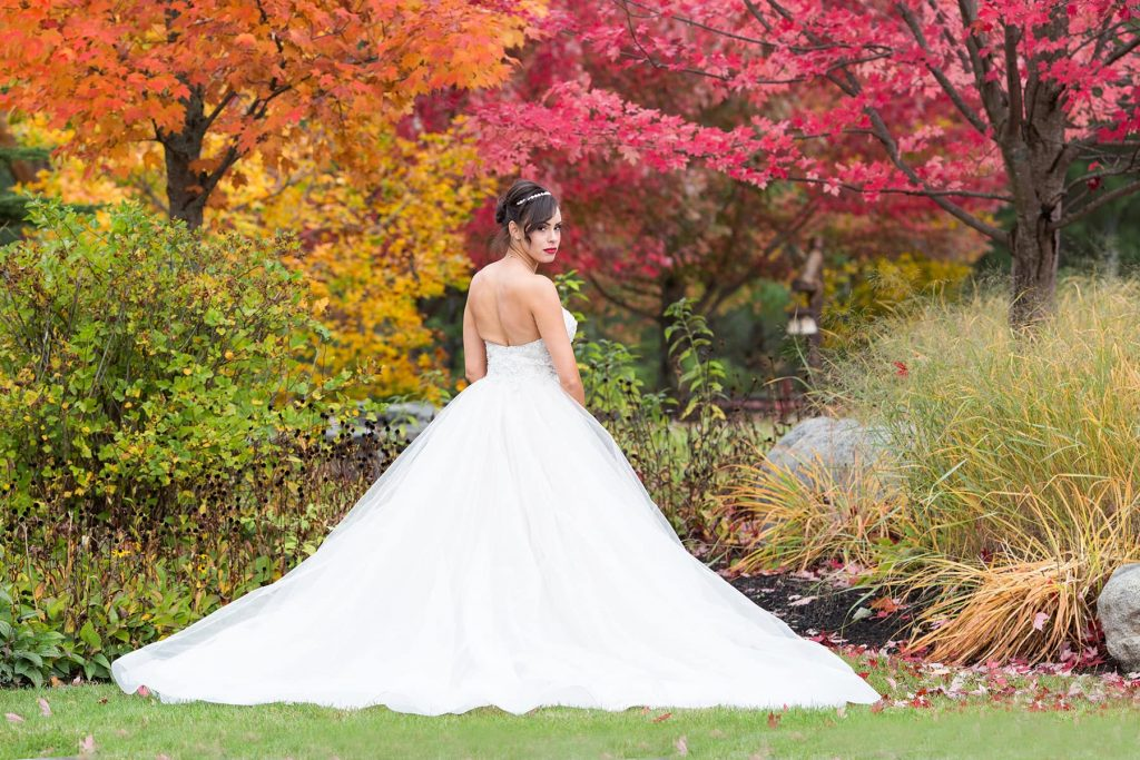 groom hides behind a tree looking at bride with beautiful blue eyes